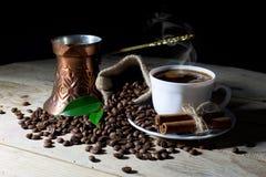 Caffè nero caldo in tazza di caffè macchiato e della caffettiera con i chicchi di caffè sul nero Fotografia Stock
