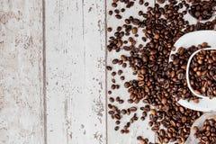 Caff? nero in chicchi bianchi di caff? e della tazza su fondo di legno leggero Vista superiore, spazio per testo immagini stock libere da diritti