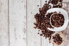 Caff? nero in chicchi bianchi di caff? e della tazza su fondo di legno leggero Vista superiore, spazio per testo fotografia stock libera da diritti