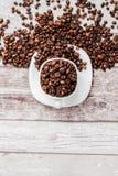 Caff? nero in chicchi bianchi di caff? e della tazza su fondo di legno leggero Vista superiore, spazio per testo immagine stock