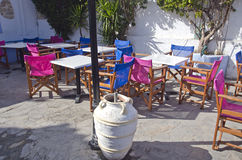 Caffe in Greece with a pot. Caffe in Greece with colorful chairs Royalty Free Stock Images