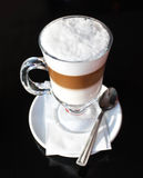 Caffe latte. Mug of layered caffe latte on a black table Royalty Free Stock Photos
