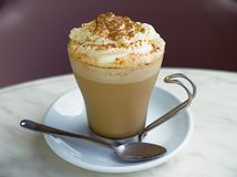 Caffe Latte. And spoon on a saucer with emphasis on the creamy top Royalty Free Stock Photography