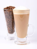 Caffe latte and coffee beans. Glass of caffe latte with a glass of coffee beans on white background royalty free stock image