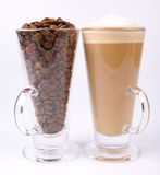 Caffe latte and coffee beans. Glass of caffe latte with a glass of coffee beans on white background royalty free stock photography