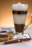 Caffe latte with donuts pen on the writing table Stock Photo