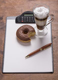 Caffe latte with donuts pen on the writing table Royalty Free Stock Photography