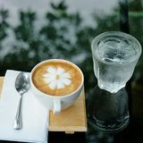 Caffe latte in the garden. Coffee on glass table with garden reflections Royalty Free Stock Photo