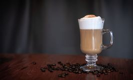 Caffe latte with generous amounts of foam. A caffe latte topped with foam and cocoa in a clear glass mug, on a wooden table with coffee beans. A dark grey royalty free stock image