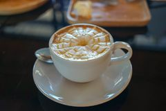 Caffe latte with latte art design in spider web flower pattern on milky foam layer in white cup and saucer with light reflection. On black glass table and Royalty Free Stock Images