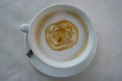 Caffe latte med lattekonst i rosa blommamodell på det mjölkaktiga skumlagret i den vita koppen och tefatet på vit texturerade tab Royaltyfria Foton