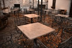 Caffe terrace in the winter. Covered with yellow leafs. No guests. Photo taken in the Old city of Kotor, Montenegro royalty free stock image