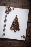 Caffee beans christmass tree. Page in notepad with christmass tree made of beans Royalty Free Stock Photography