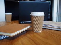 Caffeiene boost for laptop user. Two disposable coffee cups next to some desk organisers and an open laptop on a wooden surface work space Stock Photography