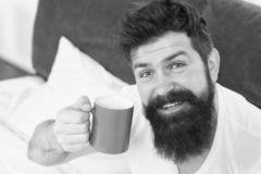 Caffeine addicted. Coffee fills you with energy. Good gay begins from cup of coffee. Coffee affects body. Man handsome. Hipster relaxing on bed with coffee cup stock photos