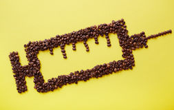 Caffeine drug. Coffee beans in shape of syringe on yellow background Royalty Free Stock Photography