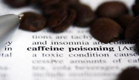Caffeine poisoning. Coffee beans and pen lying on a medical dictionary open at the caffeine poisoning page royalty free stock photos