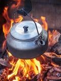 Caffettiera metallica nel calore del fuoco di accampamento Fotografie Stock Libere da Diritti