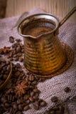 Caffettiera turca sopra i chicchi di caffè fotografia stock