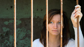 In a cage-2. Scared girl behind a lattice Stock Images