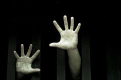 In cage. Prisoner hands stretch out from prison bars stock photography
