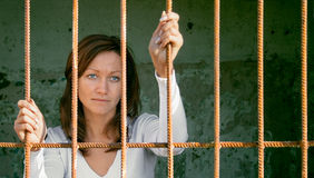 In a cage-3. Scared girl behind a lattice Royalty Free Stock Image