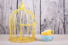 Cage and cups on table over wooden background Royalty Free Stock Photos