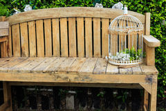 Cage en acier sur une chaise en bois Images stock