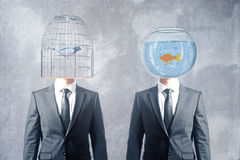 Cage and fishbowl heads. Birdcage and fishtank headed businessmen on concrete background stock photography