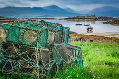 Cage for lobster and bay with boats in Scotland Royalty Free Stock Photo