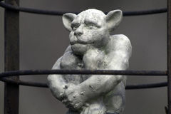 Caged. A concrete cast gargoyle I made.  He is hanging in a tree behind a small cabin waiting for Stock Photo