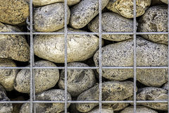 Caged stones abstract pattern. Large rocks supported by a cage. An abstract texture background with many connotations Royalty Free Stock Image
