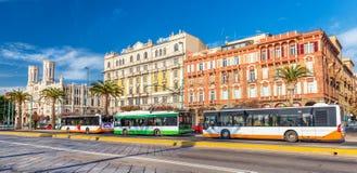 Cagliari Italien: Bussar och spårvagnen parkerade nära hållplatsen på den centrala gatan av staden Royaltyfri Bild