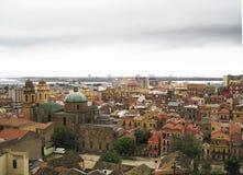 Cagliari's skyline with buildings, port, sea and gloomy grey clo. Udy sky in Sardinia stock image