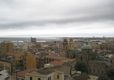Cagliari's skyline with buildings, port, sea and gloomy grey clo. Udy sky in Sardinia Royalty Free Stock Image