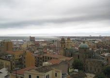Cagliari's skyline with buildings, port, sea and gloomy grey clo. Udy sky in Sardinia royalty free stock image