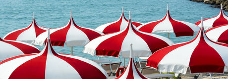Cagnes-sur-Mer (Cote d'Azur). Cagnes-sur-Mer (Alpes-Maritimes, Provence-Alpes-Cote d'Azur, France), red and white umbrellas on the beach Royalty Free Stock Photos