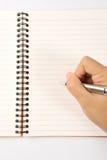Cahier à disposition crayon lecteur de main Photos libres de droits