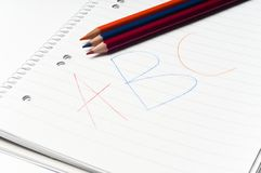 Cahier écrit avec les crayons colorés Image stock