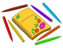 Cahier avec des fleurs et des crayons lecteurs feutres Photographie stock libre de droits