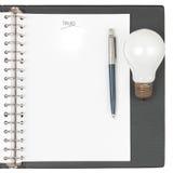 Cahier avec le crayon lecteur et l'ampoule Photographie stock