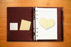 Cahier avec le papier blanc de forme de coeur Photo stock