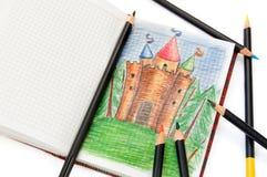 Cahier avec un croquis d'un château féerique et des crayons Image stock