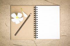 Cahier blanc avec la fleur de frangipani sur le sable image stock