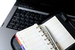 Cahier d'organisateur sur le concept de programme d'affaires de transmission d'ordinateur portatif Image libre de droits