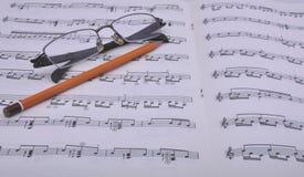 Cahier de musique et verres Images libres de droits
