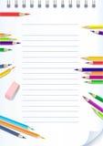 Cahier de papier avec des crayons de couleur Photographie stock libre de droits