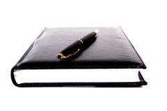 Cahier matériel noir avec le crayon lecteur. Photo libre de droits