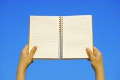 Cahier ouvert de fixation de main et ciel bleu Photographie stock libre de droits