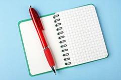 Cahier ouvert et crayon lecteur rouge Image stock